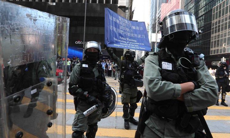Cảnh sát chống bạo động Hong Kong giơ cờ xanh để cảnh báo người biểu tình không tụ tập bất hợp pháp tại quận Central hôm nay. Ảnh: SCMP.