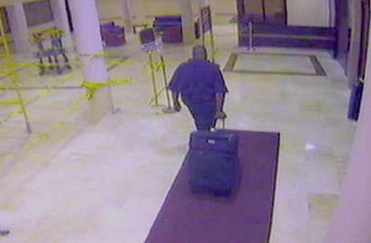 Người đàn ông da đen dắt chiếc valy ra khỏi khách sạn. Ảnh: ABC News.
