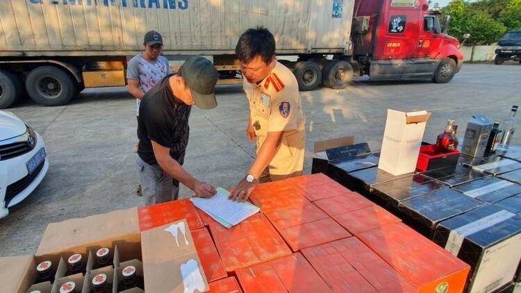 Tài xế Hà đang ký vào biên bản tạm giữ hàng hóa để kiểm tra. Ảnh: Việt Quốc