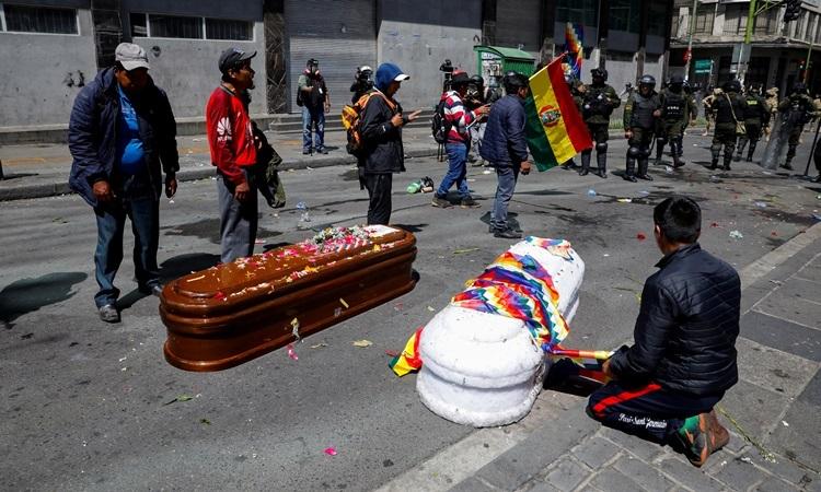 Người biểu tình bên hai trong số 5 quan tài mà họ đưa đi diễu hành ở thủ đô LA Paz, Bolivia hôm 21/11. Ảnh: Reuters.