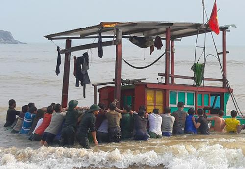 Bộ đội Biên phòng cùng người dân lai dắt thuyền gặp nạn vào bờ biển Quỳnh Viên (huyện Thạch Hà). Ảnh: Đức Hùng