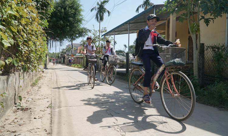 Học sinh đi học về trên đường làng được làm từ tiền phúng điếu cụ Bùi Kiệt, cha bà Phong. Ảnh: Phạm Linh.