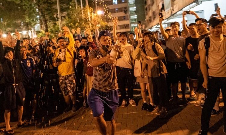 Người ủng hộ dân chủ Hong Kong ăn mừng khi kết quả bầu cử được công bố sau nửa đêm 24/11. Ảnh: NYTimes.