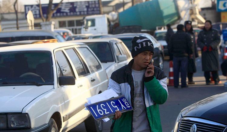 Một người cầm biển số tại chợ xe cũ ở Bắc Kinh. Photo: AFP