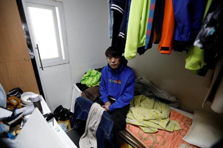 Hwang Hyeon-dong trong căn hộ hơn 6 m2 anh thuê gần trường đại học ở Seoul. Ảnh: Reuters.