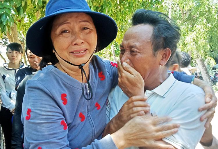 Ông Quốc khóc với người thân ngư dân mất tích khi trở về bờ. Ảnh:ChíĐại.
