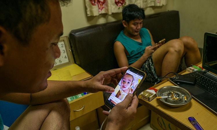 Jun Russel Reunir (trái) xem ảnh con gái trên điện thoại. Ảnh: NY Times.