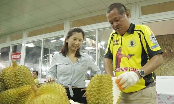 Thị trưởng Tha Chang Chalermpol Sakkham (phải) bổ một quả sầu riêng. Ảnh: CNA.