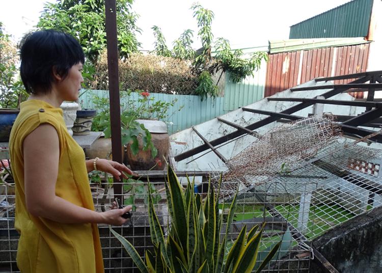 Bà Bình bên căn nhà cấp 4 cũ sắp chìm dần vì lún. Ảnh: Hà An.