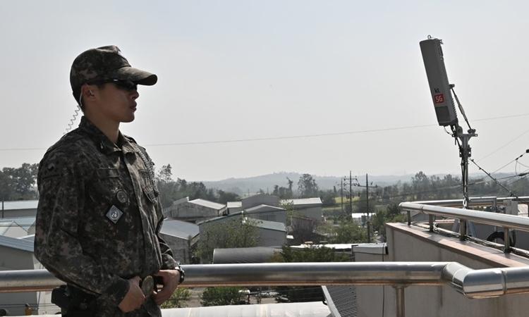 Một lính Hàn Quốc đứng gần anten mạng 5G ở DMZ hồi tháng 9. Ảnh: AFP.