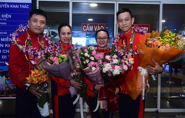 Từ trái qua là HLV Hồng Việt, HLV Thu Trang, Hải Yến và Đức Hòa, tại sân bay Nội Bài tối 2/12. Ảnh: Giang Huy.