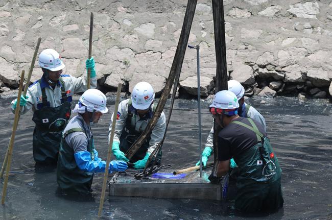 Chuyên gia Nhật Bản và công nhân lắp đặt thiết bị Nano-Bioreactor ở sông Tô Lịch ngày 16/5. Ảnh: Võ Hải