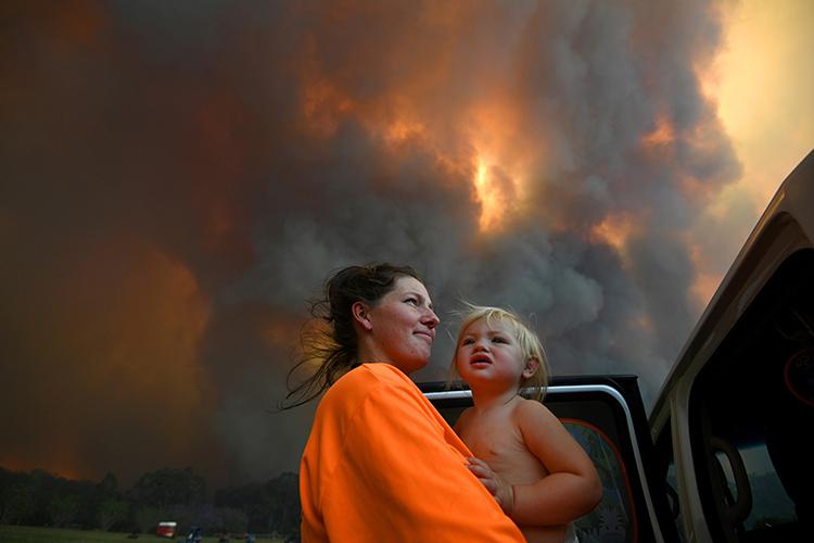 Mộtngười phụ nữ và con gái đứng giữa làn khói bốc lên từ thảm họa cháy rừng ởbang New South Wales, Australia tháng trước. Ảnh: Reuters