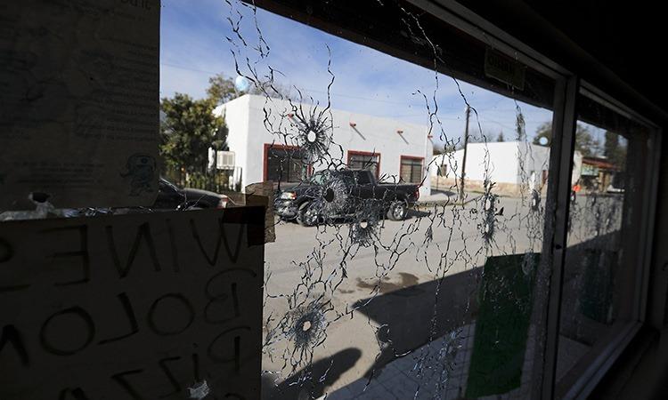 Cửa sổ chi chít vết đạn của một cửa hàng ở Villa Union, bang Coahuila, sau vụ đấu súng ngày 30/11-1/12. Ảnh: AP.