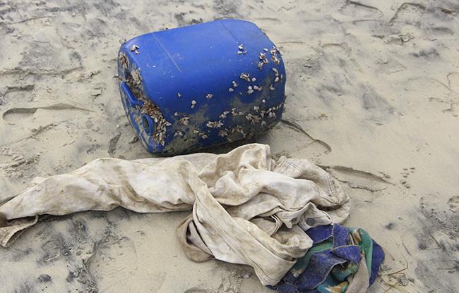 Can nhựa chứa heroin và áo quần dạt vào bờ biển ông Lộc nhặt được. Ảnh: Võ Thạnh