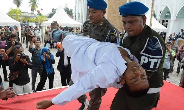 Nam thanh niên ngất xỉu sau khi bị phạt roi bên ngoài nhà thờ Hồi giáo tỉnh Aceh, Indonesia hôm nay. Ảnh: AFP.