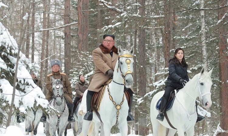 Lãnh đạo Kim Jong-un (giữa) và vợ Ri Sol-ju cùng các quan chức Triều Tiên cưỡi ngựa trên núi Paektu trong bức ảnh được truyền thông nước này đăng ngày 4/12. Ảnh: KCNA.