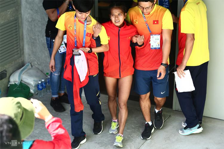 Hồng Lệ được hai đồng đội dìu từ phòng y tế ra ngoài sân để chuẩn bị dự lễ nhận huy chương. Ảnh: Phạm Đương.