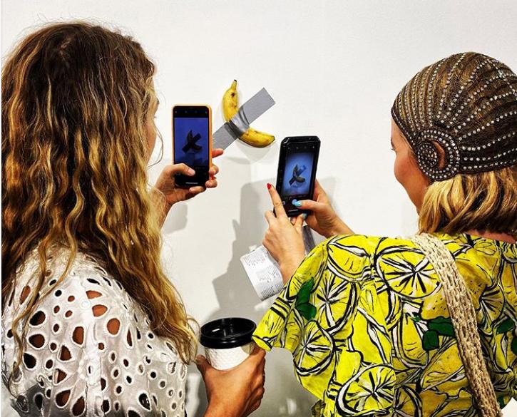 Hai khách tham quan chụp ảnh tác phẩm của nghệ sĩ Italy Maurizio Cattelantại trung tâm triển lãm Art Basel Miami Beach