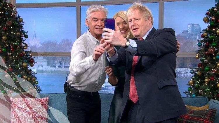 Thủ tướng Anh Boris Johnson dùng điện thoại Huawei selfie cùng MC Phillip Schofield và Holly Willoughby trong chương trình This Morning của đài ITV hôm 5/12. Ảnh: Twitter/JohnStevens.