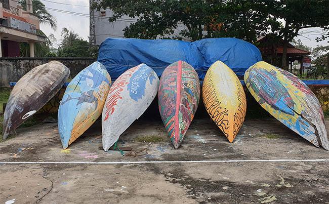 Những chiếc thuyền được vẽ tranh trưng bày bên đường đưa về cất giữ. Ảnh: Đắc Thành.