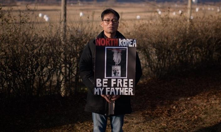 Hwang In-cheol cầm ảnh bố với dòng chữ Triều Tiên, hãy thả bố tôi khi đứng gần DMZ ngày 8/12. Ảnh: AFP.