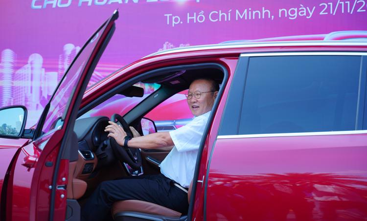 Vị HLV ngồi thử lên chiếc xe mới nhận.