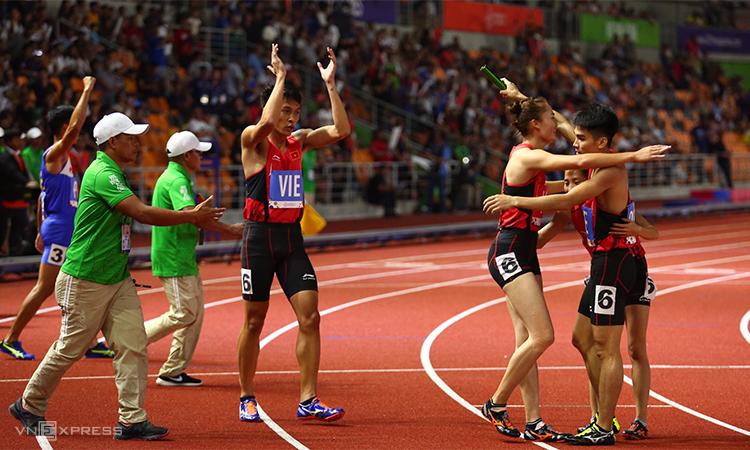 Đội tiếp sức hỗn hợp Việt Nam mừng chiếc HC vàng lịch sử - trong lần đầu tiên nội dung hỗn hợp 4 x 400 mét này được đưa vào chương trình thi đấu của SEA Games. Ảnh: Phạm Đương.