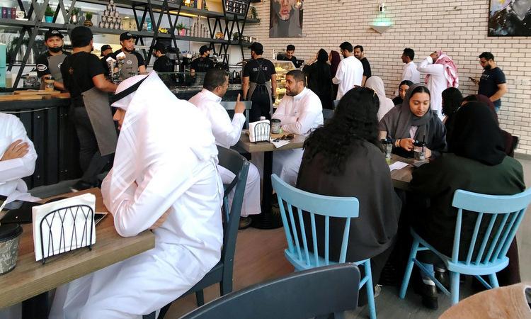 Phụ nữ, đàn ông Arab Saudi ngồi chung trong một quán cà phê ở thành phố Al Khobar hồi tháng 8. Ảnh: Reuters.