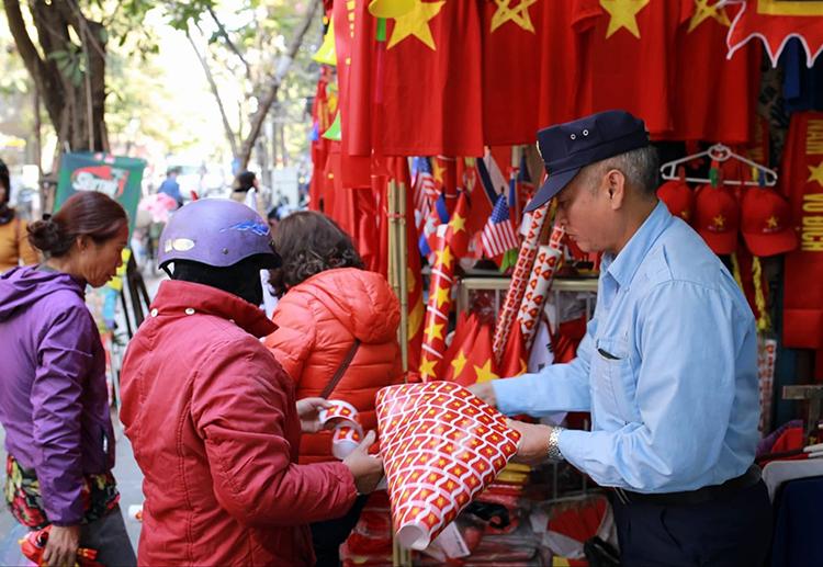 Các cửa hàng bán cờ, băng-rôn, sticker trên phố Hàng Bông (Hà Nội) đã tấp nập khách trước khi trận chung kết diễn ra. Ảnh: Tất Định.