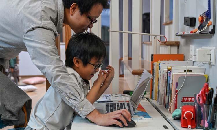 Bố của Vita hướng dẫn con lập trình một trò chơi trên máy tính tại Thượng Hải, Trung Quốc hồi tháng 11. Ảnh: AFP.