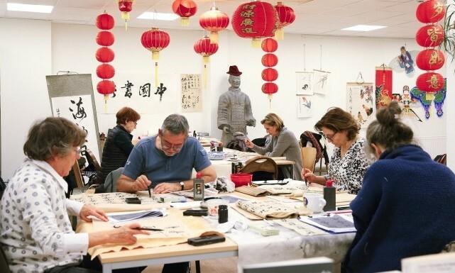 Học viên tham gia lớp học viếtthư pháp tại một Viện Khổng Tử. Ảnh: Xinhua.