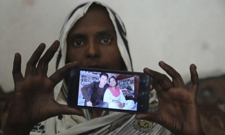 Samiya David giơ bức ảnh chụp cô và người chồng Trung Quốc ở Gujranwala, Pakistan. Ảnh: AP.