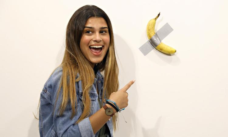 Một khách tới thăm trung tâm triển lãm Art Basel ở Miami, Mỹ chụp ảnh với tác phẩm quả chuối dán tường. Ảnh: AFP.