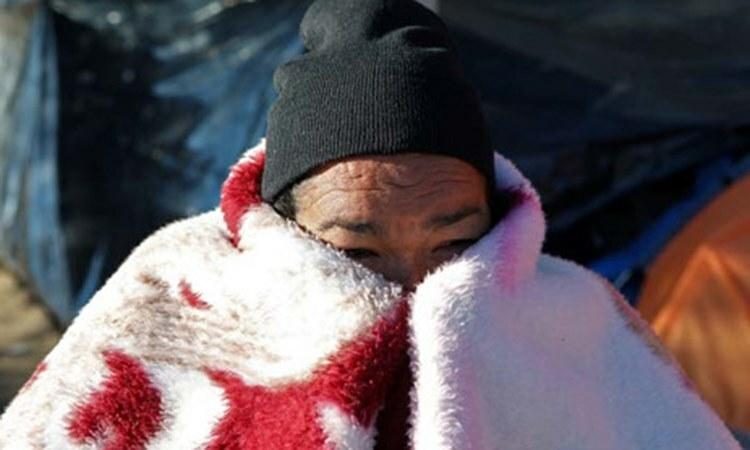 Một người tị nạn Mexico cuộn người trong chăn để chống rét tại khu lều tạm ở thành phố Ciudad Juarez, bang Chihuahua hôm 17/12. Ảnh: AFP.