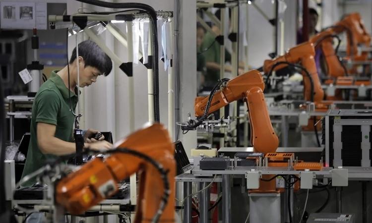 Một người làm việc với các cánh tay robot ở nhà máy tại Thâm Quyến, Trung Quốc. Ảnh: AP.