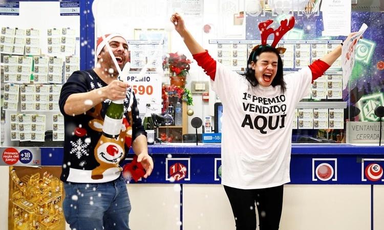 Hai chủ nhân của một gian hàng bán vé số mở rượu ăn mừng khi kết quả giải xổ số El Gordo được công bố ngày 22/12. Ảnh: Reuters.