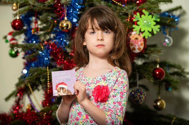 Bé Florence Widdicombe và tấm thiệp Giáng sinh có lời kêu cứu. Ảnh: AP