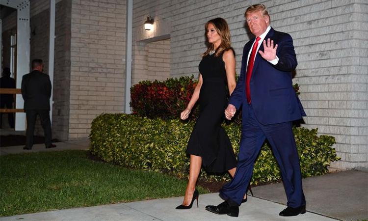 Tổng thống Mỹ và đệ nhất phu nhân Melania rời khỏi nhà thờ Family ở Florida đêm 24/12, sau khi tham dự buổi lễ. Ảnh: AFP.