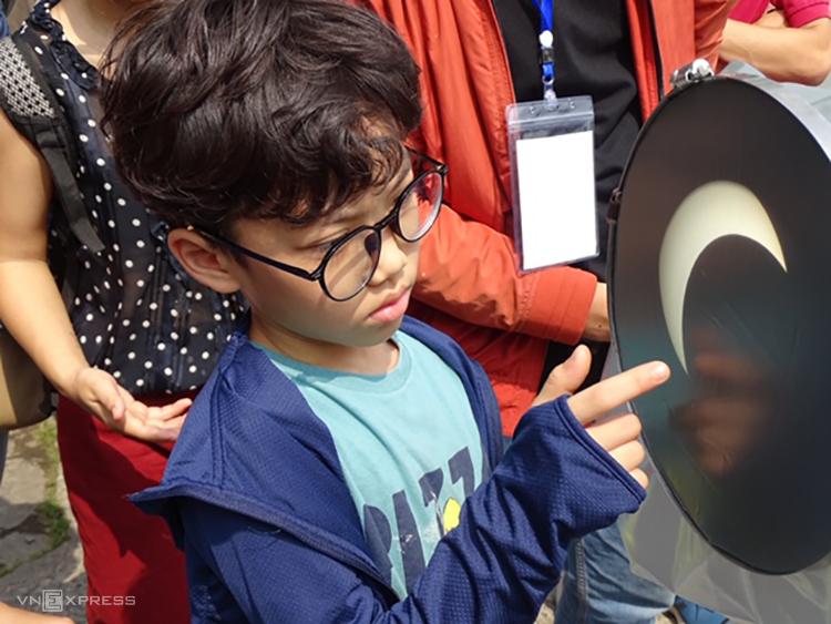 Một em nhỏ xem nhật thực ở mức cực đại qua màn hứng ảnh từ kính thiên văn tại. Ảnh: Hà An