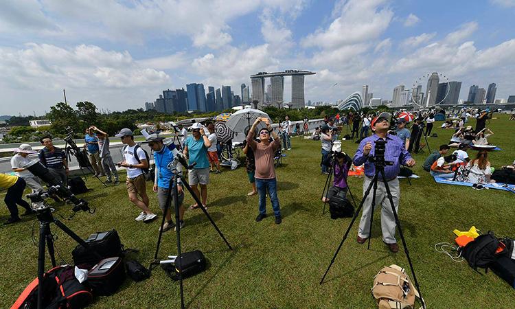 Khoảng 1.000 người yêu thiên văn đã tập trung gần con đập Marina Barrage ở Singapore để quan sát nhật thực. Ảnh: Jeremy Long