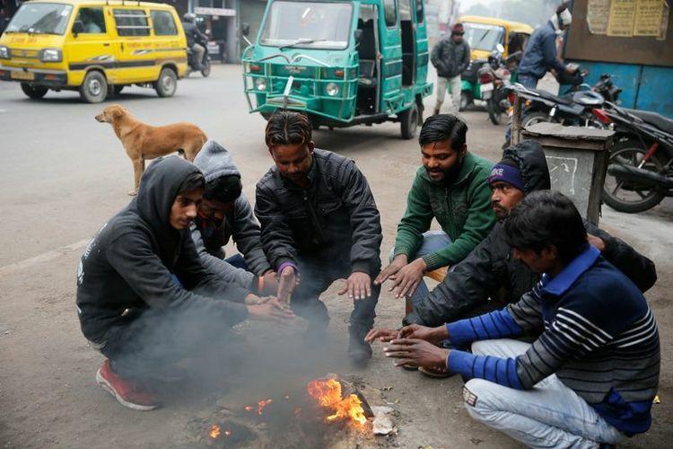 Người Bangladesh sưởi ấm bên đống lửa trên đường. Ảnh: AP.