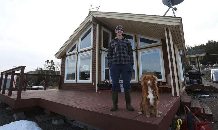 Mike Parsons đứng trước ngôi nhà của ông ở Little Bay Islands . Ảnh: Washington Post.