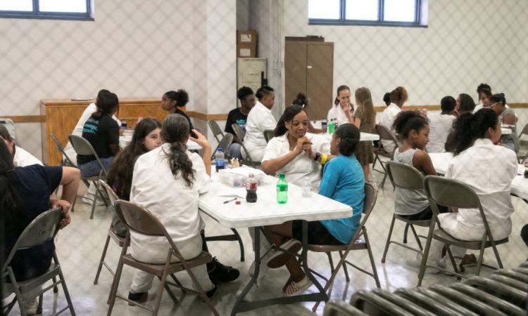 Các nữ tù nhân ngồi bên con gái tại nhà tù ở Texas. Ảnh: NY Times.