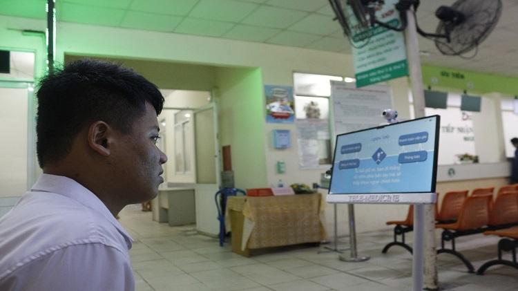Người bệnh được robot hướng dẫn nhập thông tin. Ảnh: NVCC