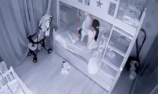 Bà Doan lúc cầm chân dốc ngước bé 14 tháng tuổi (vòng tròn đỏ). Ảnh: Cắt từ video.
