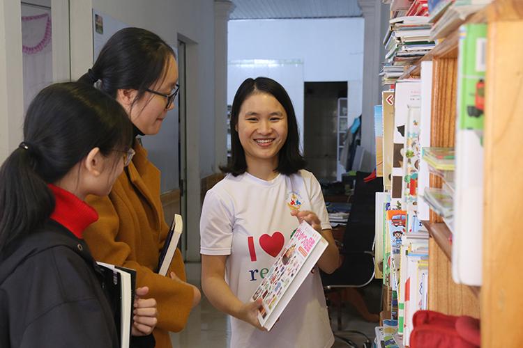 Chị Phương (phải) giới thiệu cuốn sách tiếng Nhật đến hai bạn nữ sinh lớp 12.Ảnh: Hoàng Táo