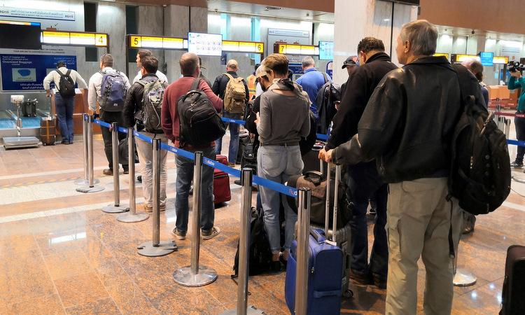Công nhân dầu mỏ Mỹ xếp hàng tại sân bay Basra để rời Iraq hôm 3/1. Ảnh: NY Times.