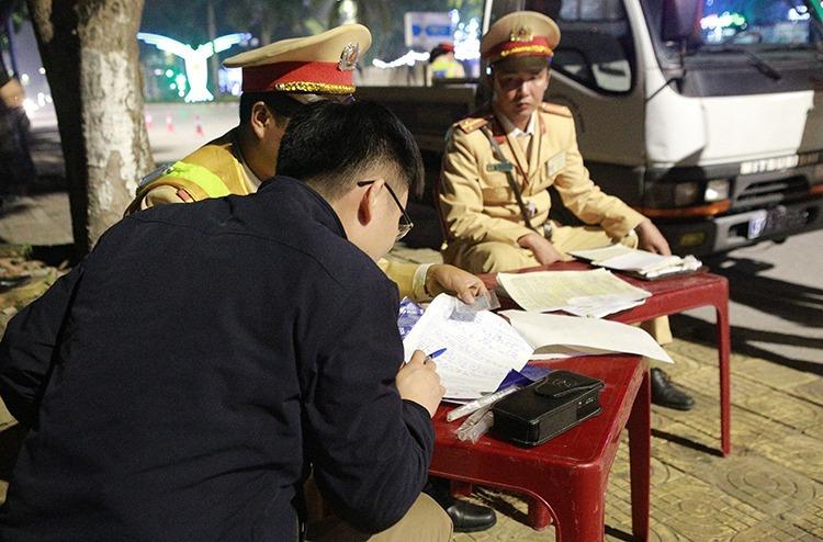 Tài xế (áo đen) soát lại nội dung vi phạm để ý vào biên bản. Ảnh: Nguyễn Hải.