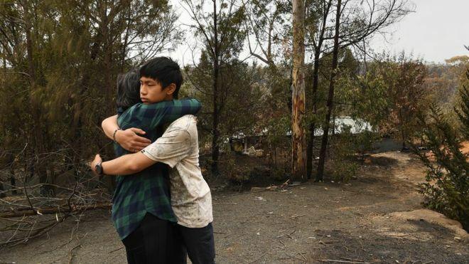 Gabriel ôm mẹ sau khi nhà bị lửa thiêu rụi. Ảnh: Sydney Morning Herald